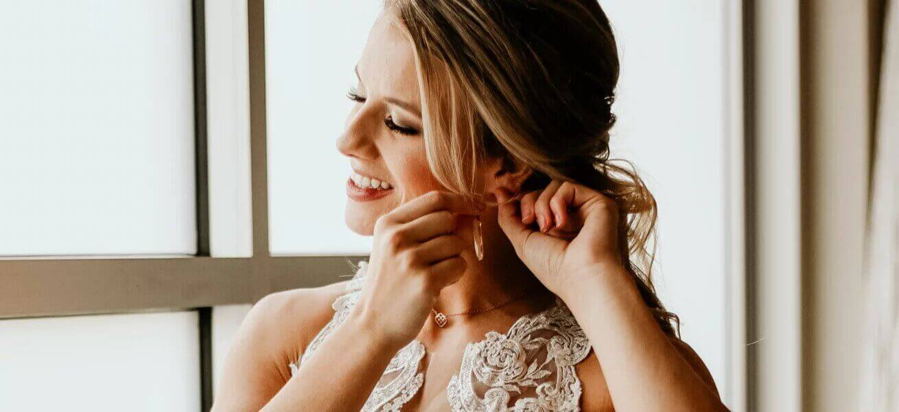 Photo of bride puting on Bestow Bridal earrings